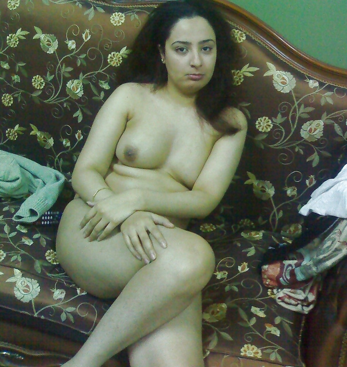 Cute girl sitting naked on the couch